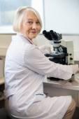 Zuversichtlich weibliche wissenschaftler mit mikroskop im labor — Stockfoto