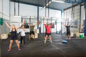Instructor Assisting Athletes In Lifting Barbells — Stock Photo
