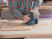 Carpenter Using Electric Planer On Wooden Plank — Stock Photo