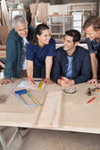 Female Carpenter Working On Blueprint With Team — Stock Photo