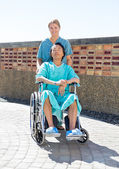 Nurse Pushing Relaxed Patient On Wheelchair At Courtyard — Stockfoto