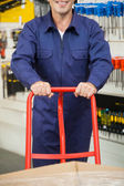 Worker Pushing Trolley In Hardware Store — Stock Photo