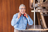 Happy Carpenter Holding Ear Protectors By Bandsaw — Stock Photo