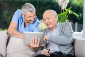 Male Nurse And Senior Man Smiling While Using Tablet Computer — Foto de Stock