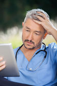 Tensed Male Caretaker Using Tablet PC — Stock Photo