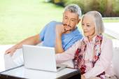 Male Caretaker And Senior Woman Using Laptop — Stock Photo