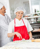 Confident Chef Cutting Ravioli Pasta With Colleague In Backgroun — Stock Photo