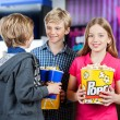 Girl Holding Popcorn While Brothers Talking At Cinema — Stock Photo #58857253
