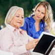 Granddaughter Looking At Grandmother Reading Book — Stock Photo #58858245