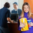 Smiling Woman Holding Snacks While Man Buying Movie Tickets — Stock Photo #58859117