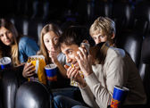 Angry Family Looking At Man Using Mobilephone In Theater — Stock Photo