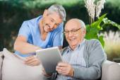 Happy Caretaker And Senior Man Using Tablet PC — Stock Photo