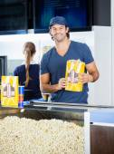 Happy Worker Holding Popcorn Paperbag At Concession Stand — Stock Photo