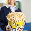 Happy Worker Offering Popcorn At Cinema Concession Stand — Stock Photo #58996813