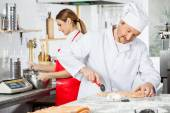 Chef Cutting Ravioli Pasta With Colleague Whisking Batter In Kit — Stock Photo