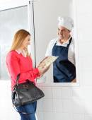 Happy Woman Purchasing Ravioli Pasta Packet From Chef — Stock Photo