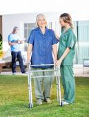 Nurse Helping Senior Woman To Use Walking Frame In Lawn — Stock Photo