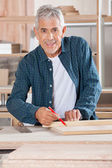 Happy Senior Carpenter Marking On Wood With Pencil — Stock Photo