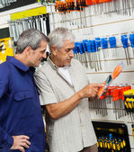 Customer Examining Packed Screwdriver While Vendor Looking At — Stok fotoğraf