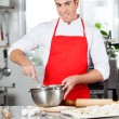 Smiling Chef Mixing Batter In Bowl To Prepare Ravioli Pasta — Stock Photo #61607861