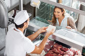 Butcher Showing Meat To Customer At Butchery — Stock Photo
