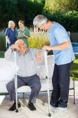 Male And Female Caretakers Helping Senior People — Stock Photo