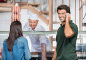 Happy Man On Call While Woman Buying Meat — Stock Photo