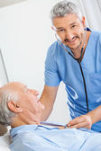 Happy Caretaker Examining Senior Man With Stethoscope — Stock Photo