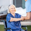Senior Woman On Wheelchair Being Assisted By Nurse — Stockfoto #61683713