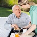 Female Caretaker Serving Breakfast To Senior Man — Stock Photo #61785449