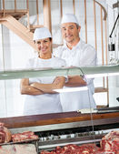Confident Butchers Standing At Meat Counter — Stock Photo
