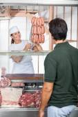 Butcher Selling Sausages To Customer At Shop — Stock Photo