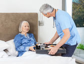 Nurse Serving Breakfast To Senior Woman On Bed — Stock Photo