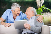 Laughing Caretaker And Senior Man Using Tablet Computer — Stock Photo