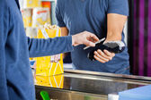 Man Using NFC Technology To Make Payment At Cinema — Stock Photo
