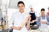 Smiling Chef Holding Rolling Pin While Colleagues Preparing Past — Stock Photo