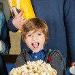 Portrait Of Excited Boy Showing Popcorn At Cinema — Stock Photo #62244323