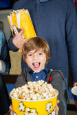Portrait Of Excited Boy Showing Popcorn At Cinema — Stock Photo