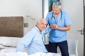 Senior Man Being Assisted By Male Caretaker In Bedroom — Stock Photo