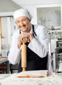 Chef Holding Rolling Pin At Counter In Kitchen — Stock Photo