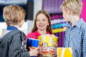 Siblings Conversing While Holding Snacks At Cinema — Stock Photo