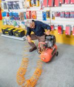 Senior Man Examining Air Compressor In Shop — Stok fotoğraf