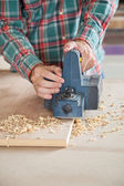 Carpenter Using Electric Planer On Plank — Stock Photo