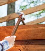 Workers Hand Hammering Nail On Timber Frame At Site — Stock Photo