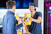 Worker Selling Popcorn To Man At Concession Stand — Stock Photo
