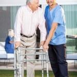Smiling Caretaker Assisting Senior Man To Use Walking Frame — Stock Photo #64289725