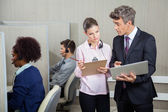 Business People With Clipboard And Laptop Discussing In Call Cen — Stock Photo