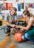 Saleswoman Showing Air Compressor To Customer In Store — Stock Photo