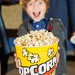 Portrait Of Excited Boy Offering Popcorn Bucket At Cinema — Stock Photo #69996449