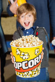 Portrait Of Excited Boy Offering Popcorn Bucket At Cinema — Stock Photo